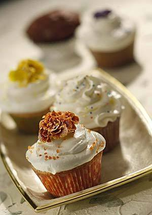 Sugar-dusted flowers are used to decorate butter cupcakes.
