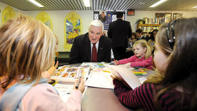Gov. Tom Corbett, center, talks with children at the Osterhout Free Library, Wilkes-Barre, Wednesday. Corbett was at the library to discuss the Children¿s Health Insurance Program.