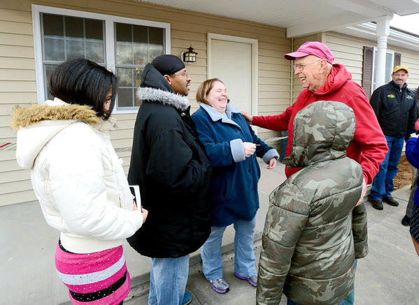 Bruce Sperow, project manager on the Habitat for Humanity home built for the Carr family in Martinsburg, W.Va., offers congratulations and the keys on Wednesday. The family is, from left, Cierra Carr, 14, Wendell Carr his wife Tara Carr, and Devon Carr, 12.