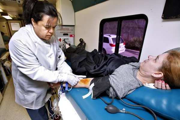 "Blood donor Brenda Gant of La Crescenta is helped by American Red Cross Tech Norma Svanoe during the annual county-wide L.A. County Sheriff's ""Battle of the Badges"" at the La Crescenta Valley Station."