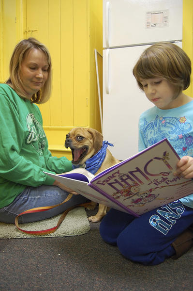 Nora Dickey reads to Sassy, a puggle, and Antietam Humane Society Executive Director Andrea Haugh on Wednesday.