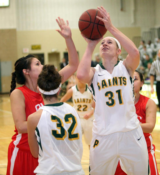 Presentation College's Kelli Boekelheide (31) puts up a shot between Oglala Lakota College's Alyssa Looks Twice, left and Holly Jo Clifford, back right, as PC's Rachel Fuhrmann (32) looks on during the first half of Wednesday night's game at the Strode Activity Center.