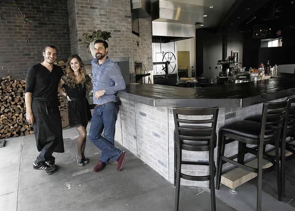 Noah Blom, let, with his wife, Marin Howarth, and Koire Rogers, right, are opening a new restaurant, Arc, in Costa Mesa's South Coast Collection on Friday.