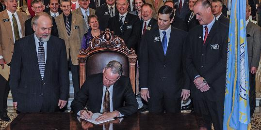 Governor Dennis Daugaard signs Senate Bill 70, the Justice Reform Bill, into law during a  ceremony at the capital on Wednesday.