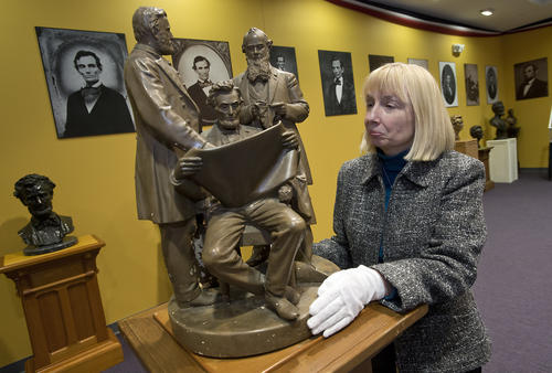 Lehigh Valley Heritage Museum Assistant Director Jill Youngken reviews a statue from 1868, which depicts Lt. General Ulysis S. Grant (left), Secretary of War Edwin Stanton and President Abraham Lincoln is part of the new exhibit on Abraham Lincoln.