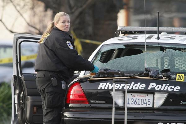 Riverside police investigate the scene where two fellow officers were shot, one fatally, early Thursday. Police suspect Christopher Jordan Dorner, a former LAPD officer, in the shootings and those of another police officer in Corona and a couple in Irvine earlier this week.