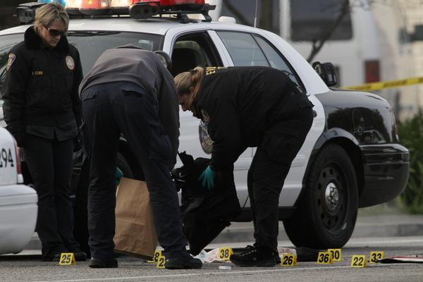 Riverside police investigators tag and bag evidence at the scene where two fellow officers were shot early Thursday. One was killed and the other was in critical condition.