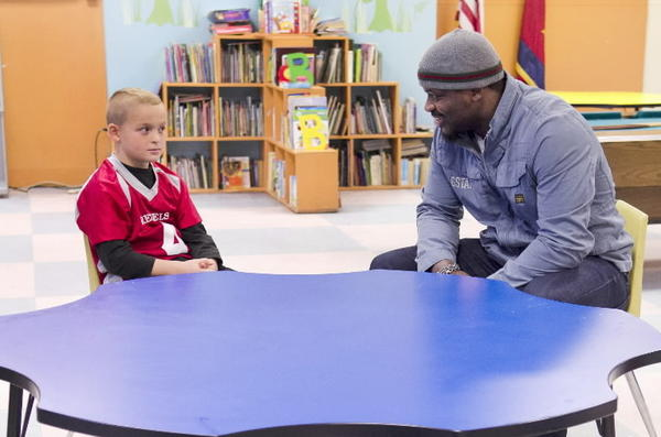 Jameel McClain a a boy he extends a helping hand to in a USA cable channel documentary airing Friday.