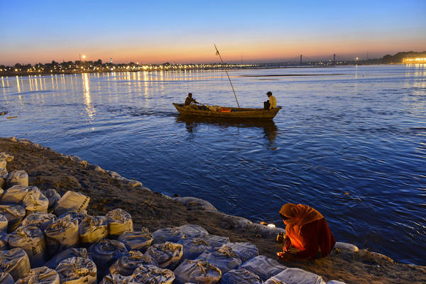 A woman prays by a candle light as two men use a boat to make their way upstream in the confluence of the Yomuna and the Ganges river at the Sangam during the Maha Kumbh festival in Allahabad on February 7, 2013. The Kumbh Mela in the town of Allahabad will see up to 100 million worshippers gather over 55 days to take a ritual bath in the holy waters, believed to cleanse sins and bestow blessings.