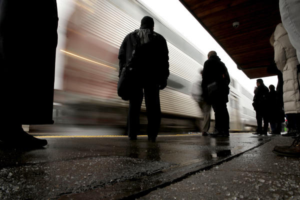 Commuters wait at a salted Barrington Metra station during the light rain on Thursday morning.
