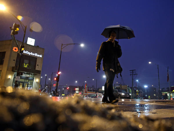 A man crosses North Milwaukee Avenue at Western Avenue in the rain Thursday morning