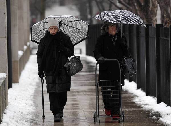 Two ladies walk with umbrellas behind the Museum of Contemporary Art. Rain is forcasted to turn to sleet and then to snow as the day goes on.