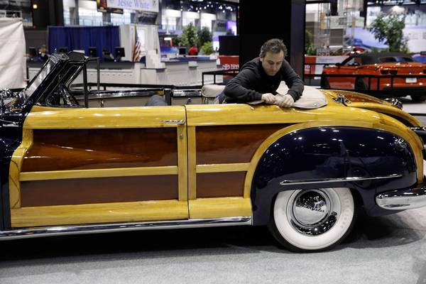 Stephen Murphy drops the top on Richard Driehaus' 1947 Chrysler Town & Country on display at the at the Classic Car Club of America booth at the 105th Chicago Auto Show at McCormick Place.