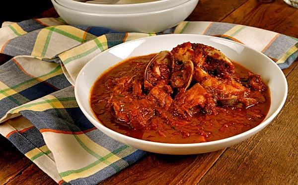 Cioppino basics are wine, tomatoes and assorted seafood.