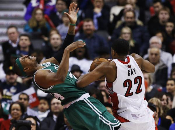 Toronto Raptors' Rudy Gay commits an offensive foul on Boston Celtics' Paul Pierce.