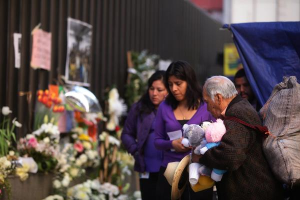 Employees of oil company Petroleos Mexicanos, or Pemex, leave flowers as they return to work Wednesday in the complex where a deadly explosion occurred last week.