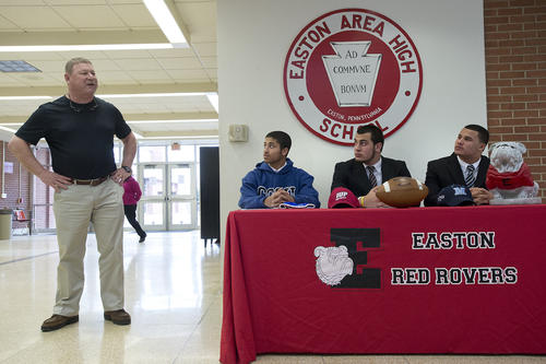 Easton High School head coach Steve Shiffert speaks to the news media beside (from left) football athletes Xavier Jenkins, 17, of Easton, Matthew Mowad, 17, of Easton and Austin Brown, 17, of Forks Township, attend Division 1 signing event in the school's gym on Thursday, February 7. 2013.