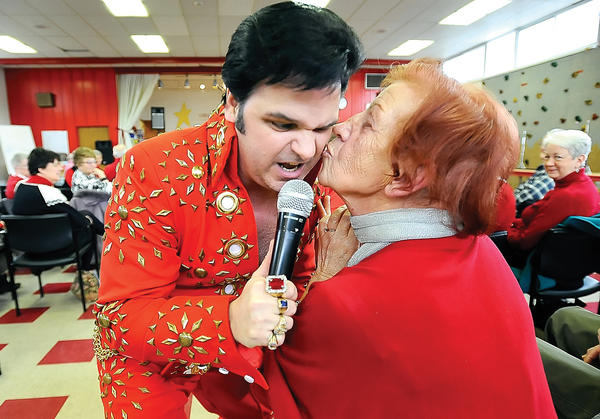 Elvis tribute artist Kevin Booth of Martinsburg, W.Va., left, rocked the house at Girls Inc. in 2012 for a Valentine's Day Elvis concert and received a kiss on the cheek from Anna Laub, right, of Hagerstown.