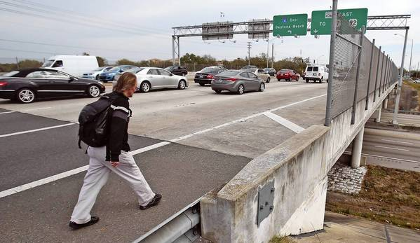 A pedestrian walks across the SR436 bridge over Interstate 4 on Thursday in Altamonte Springs.