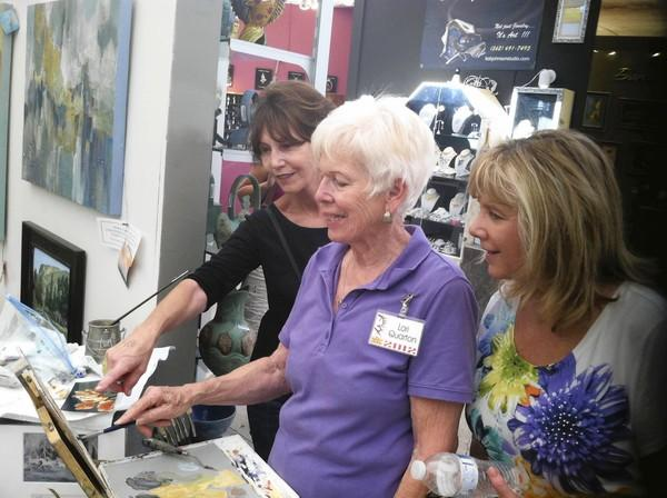Painter Lori Quarton with customers Donna Wilson and Sandi Landon, who are admiring her painting technique, seen at last summer's Art-A-Fair.