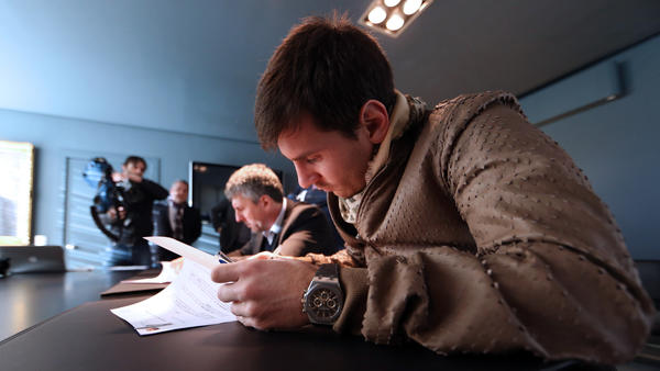 Lionel Messi puts pen to paper as he signs a two-year contract extension that will keep him with FC Barcelona through 2018.