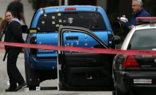 Police investigators work around a blue pickup truck riddled with bullets in the 19500 block of Redbeam Avenue in Torrance after a police protection team fired on it. The officers were protecting the neighborhood in the wake of threats against an officer, allegedly by former LAPD Officer Christopher Jordan Dorner.