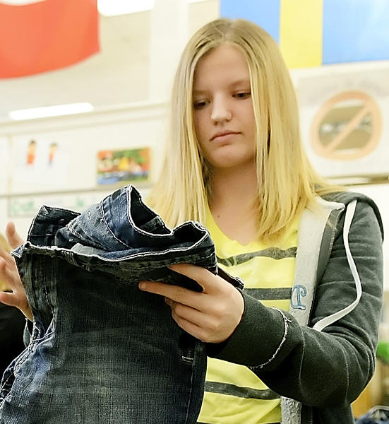 Springfield Middle School student Amanda Curry folds jeans that will be given to needy people through the Teens for Jeans program.