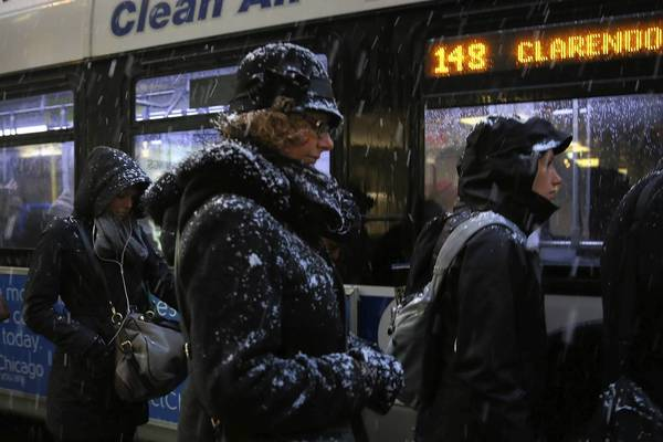 Commuters wait to board a bus as snow falls on Michigan Avenue in Chicago.