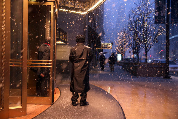 Hotel InterContinental doorman Clive Blake watches as snow falls on Michigan Avenue in Chicago.