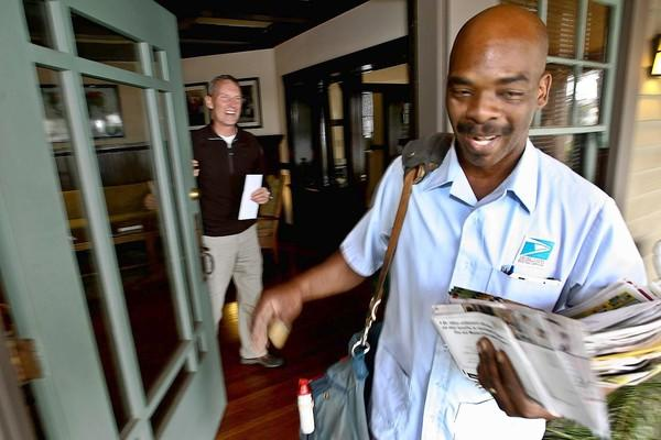 The financially struggling U.S. Postal Service says it will stop delivering mail on Saturdays starting in August. Above, Thomas Carter, who has been a letter carrier since 1986, delivers mail in Pasadena.