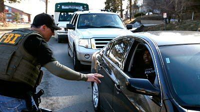 An FBI agent checks cars as they leave a Big Bear ski resort in the search for suspect Christopher Dorner. The resort was closed after he was believed to be in the area.
