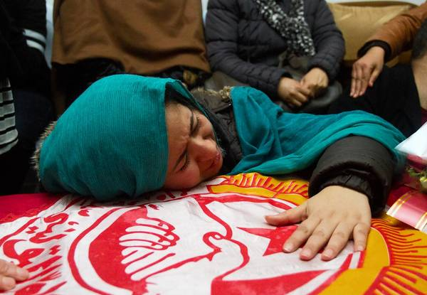 A relative cries over the coffin of slain opposition leader Chokri Belaid at his parents' home near Tunis, Tunisia.