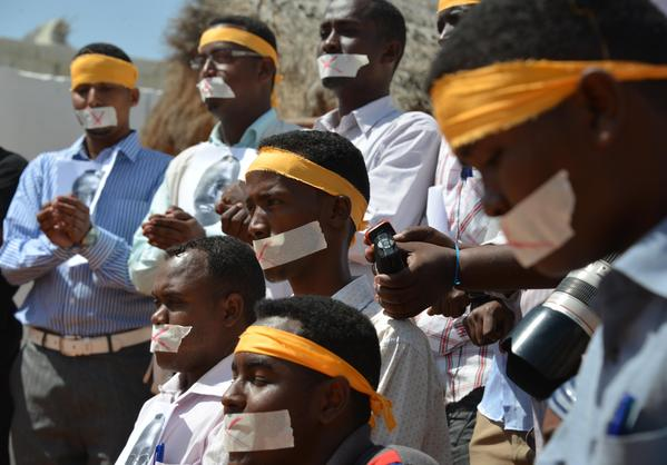 Somali journalists hold up the picture of arrested journalist Abdiaziz Abdinur Ibrahim at an event condemning his detention in Mogadishu. Ibrahim had interviewed a Somali woman who'd allegedly been raped by security forces. She has also been detained.