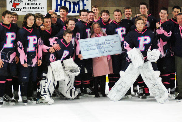The Petoskey Northmen hockey team presents a check to Alison Hubbard, the giving manager from McLaren Northern Michigan Hospital following Wednesday's second annual Pink in the Rink Game against Gaylord at Griffin Arena. The Northmen defeated the Blue Devils, 2-1.