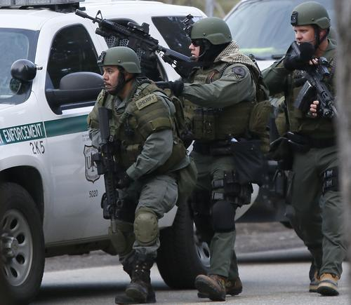 SWAT officers move toward a home on Club View Drive in Big Bear Lake as the manhunt continues for Christopher Jordan Dorner. A truck believed to be his was found burning in a remote area near a ski resort, authorities said.