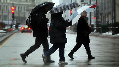 Pedestrians deal with the rain and cold along North Michigan Avenue today.