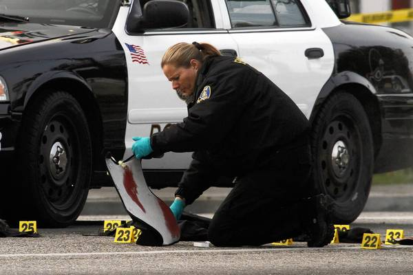A RIVERSIDE POLICE investigator studies the crime scene at Arlington and Magnolia avenues in Riverside where two Riverside police officers were shot. One officer was killed and the other is expected to survive.