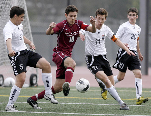 La Canada High School's #16 Aidan Tourani battles for the ball vs. South Pasadena's #5 Oscar Jaime, left, and #11 Charlie Slocum during game vs. South Pasadena High School at the Tigers home field in South Pasadena on Thursday, February 7, 2013.  #20 is Zack Dunn. The teams tied, 0-0, making them Rio Hondo League co-champs.