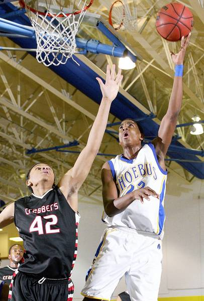 Rob Ostermaier/Daily Press Photo Joshua Davis of Phoebus gets the shot past Tre Perry of Hampton during the first half Thursday at Phoebus.