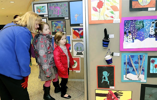 Jayn Stewart, left, and her grandaughters Sophia and Charlotte Williams look at art work on display at the Elementary Arts Festival held at South Hagerstown High School Thursday night.