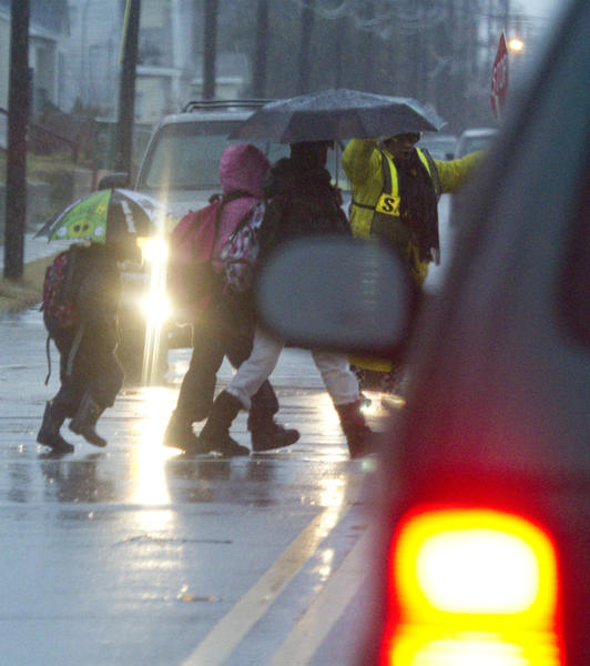 A crossing guard holds traffic as students hurry in the rain across 16th street in Hampton early Friday morning.