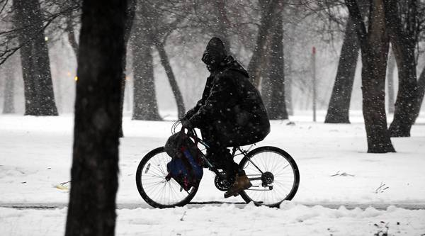 A bicyclist doesn't let the snow stop him as he makes his way along Garfield Park in Chicago.