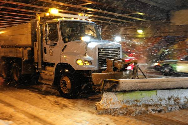 A Chicago snowplow passes under Lake Shore Drive on Foster Avenue during a rush-hour snowstorm.