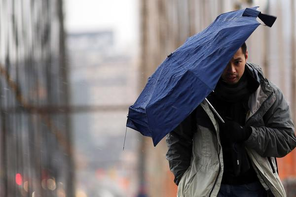 An umbrella takes a battering as a man walks across the Brooklyn Bridge in the early hours of a major winter storm.