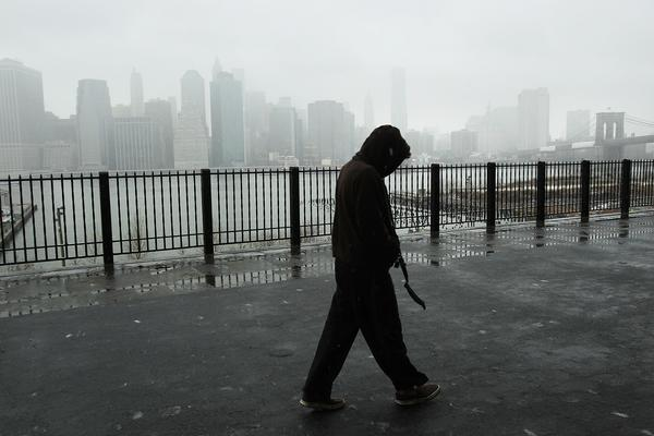 A man takes a morning walk along the promenade in Brooklyn Heights as Lower Manhattan stands in a cloud of snow and sleet.