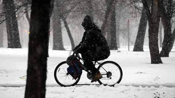 A bicyclist doesn't let the snow stop him as he makes his way along Garfield Park Thursday.