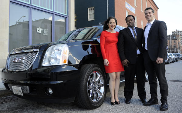Rachel Holt, left, general manager of the Uber Washington DC office; Uber driver Motti Edossa, center; and Dan Might, right, associate general manager of the Uber Baltimore office, stand with one of the cars that can transport passengers in Baltimore.
