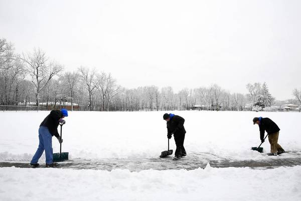 Employees of the Park District of Highland Park shovel snow the old-fashioned way at Lincoln Park in Highland Park after an equipment break-down.