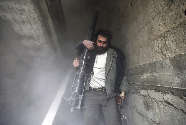 A Free Syrian Army fighter walks through a dust-filled stairwell after a comrade fired a B-10 gun at Syrian Army soldiers in the Haresta neighborhood of Damascus.