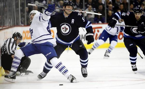 Winnipeg Jets defenseman Mark Stuart (R) and Toronto Maple Leafs forward Nazem Kadri (L) battle for the puck.